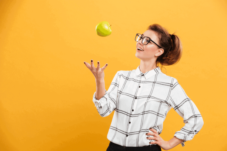 woman tossing apple into the air