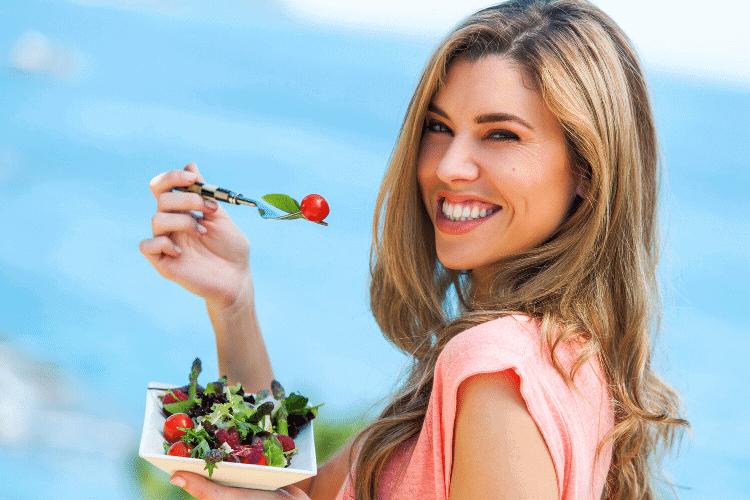 Happy woman eating fruit